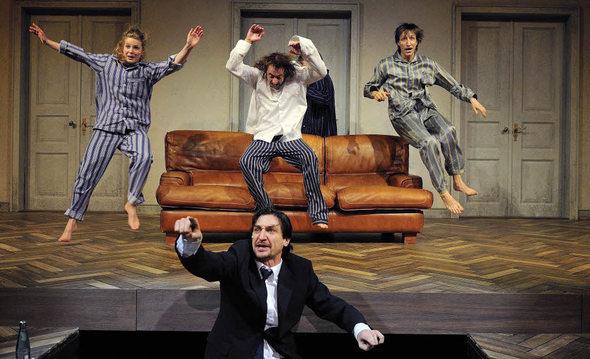 Victor Calero als Fernseher im Vordergrund, im Hintergrund fliegen Jenny Langner, André Benndorff und Hendrik Heutmann in Richtung Sofa